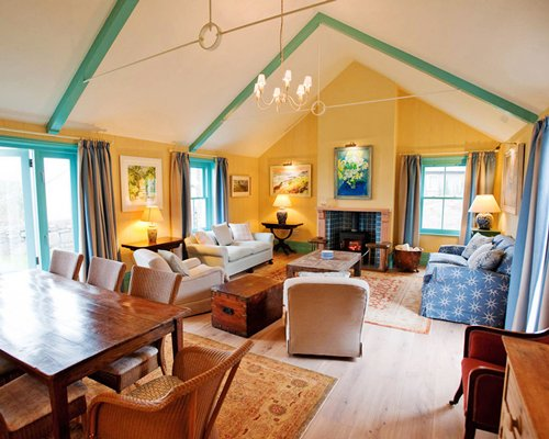 An open plan furnished living and dining area with a fire in the fireplace.