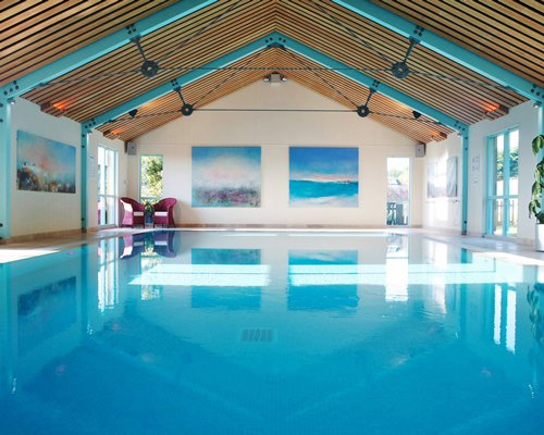 An indoor pool with patio furniture.