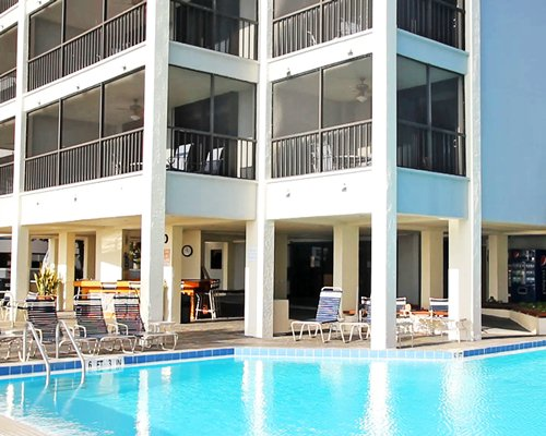 Exterior view of multiple suite balconies with swimming pool and chaise lounge chairs.