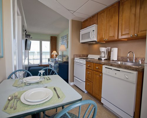 A well equipped kitchen with dining alongside living room.