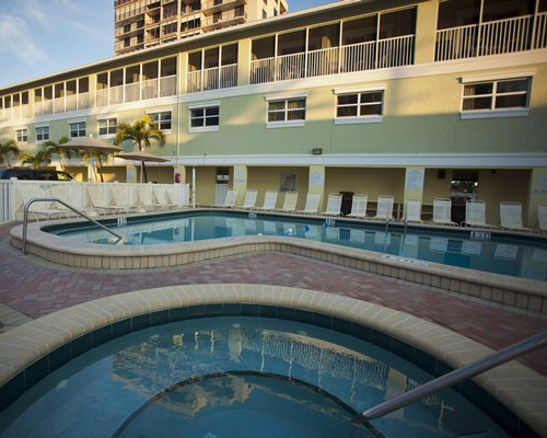 An outdoor swimming pool and hot tub alongside resort suites.