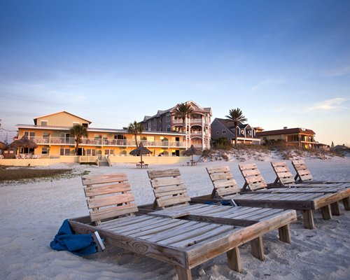 Beach view of chaise lounge chairs alongside Hideaway Sands Resort.