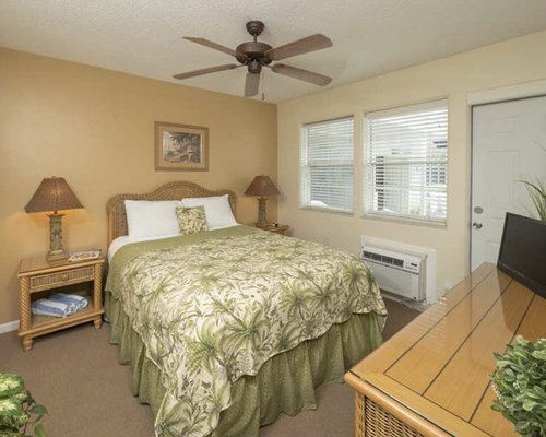 A well furnished bedroom with a queen bed and an outdoor view.