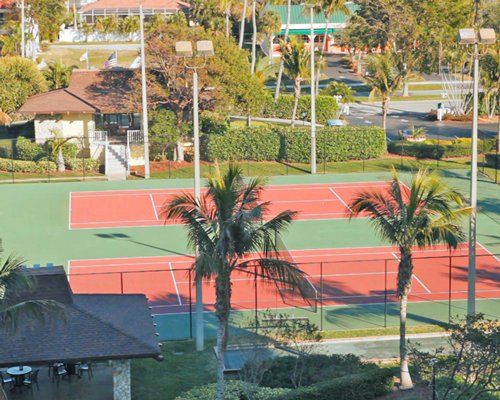 Two outdoor tennis courts alongside resort units and trees.