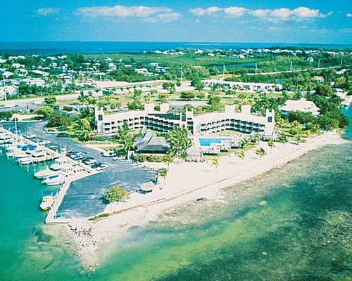 An aerial view of the Caloosa Cove Resort alongside the ocean and surrounded by a wooded area.