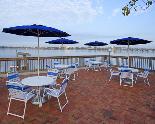 An outdoor dining area with sunshades patio tables patio chairs and a view of water.