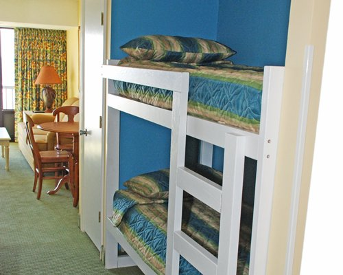 Twin bunk beds adjacent to an open plan dining area.