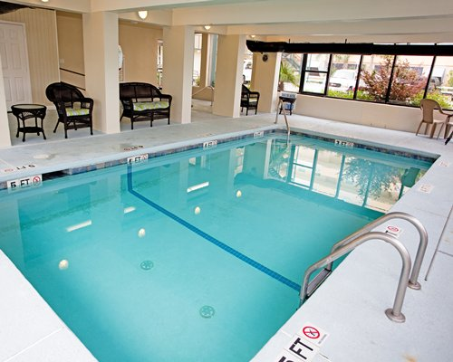 Indoor swimming pool with chairs and an outside view.