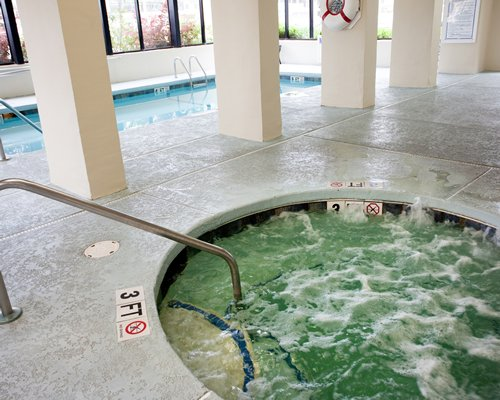 A circular indoor hot tub alongside a swimming pool.