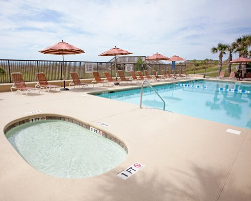 An outdoor swimming pool accompanied by a kiddie pool with chaise lounge chairs and sunshades.