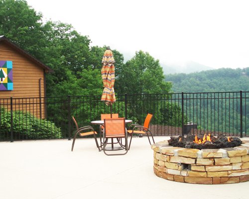 Picnic area with patio furniture and a fireplace with a forested backdrop.