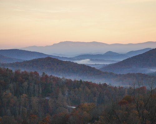 View of wooded area surrounded by mountains in the fall.