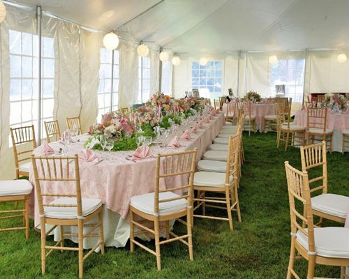 Lawn area covered with a tent that encompasses large dining tables surrounded with exquisite wooden chairs.
