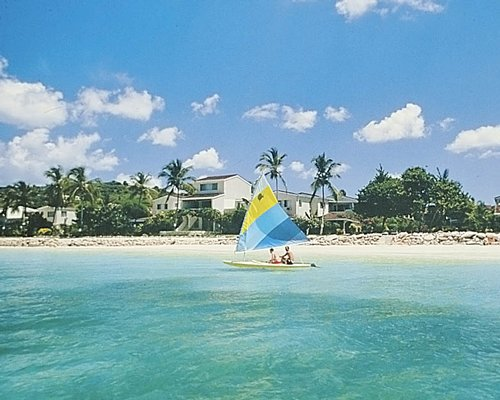 Two people in a sailboat on the ocean in front of the Antigua Village Beach Club.