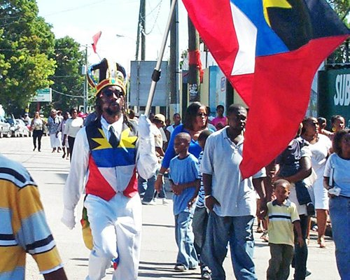 A man with an Antigua and a Barbados Flag walking on a crowded street.