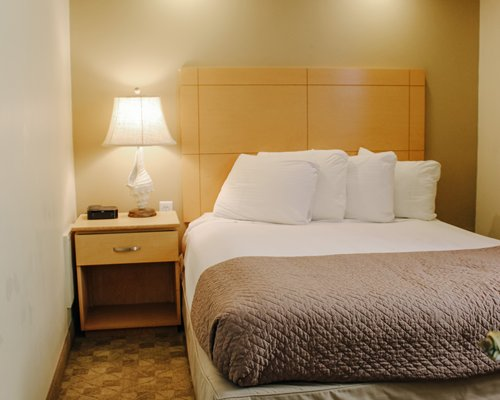 A well furnished bedroom with a television and two double sized beds.