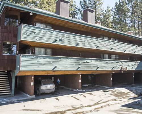 An exterior view of some of the Snow Lake Lodge accommodations alongside a wooded area.