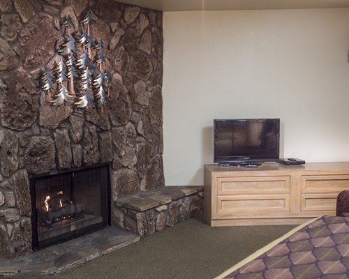 A portion of a living area with a television and fireplace.