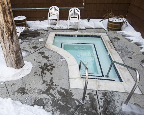 An outdoor hot tub with patio chairs surrounded by snow.