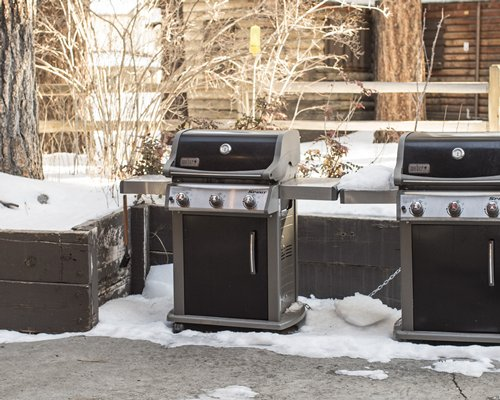 Two snow covered outdoor barbecue grills.
