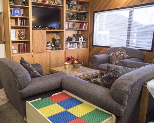 A well furnished living room with television bookshelf and outside view.