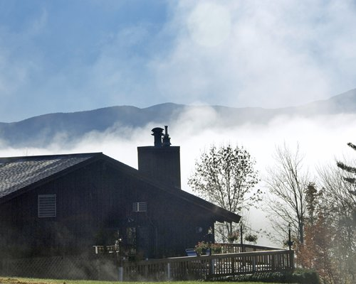 An exterior view of a resort unit among fog and mountains.