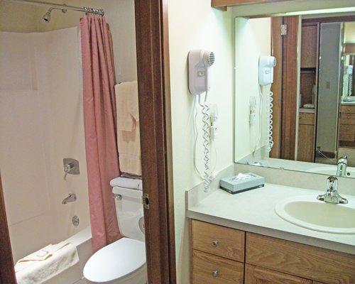 A bathroom with a bathtub shower and sink vanity.