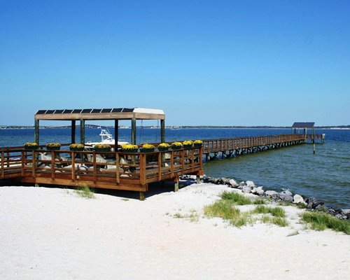 Beach view of water with a wooden pier.