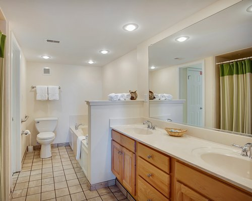 A bathroom with a bathtub and a double sink vanity.