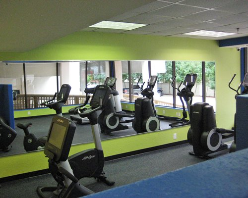 Indoor fitness area with exercise equipment with an outside view.