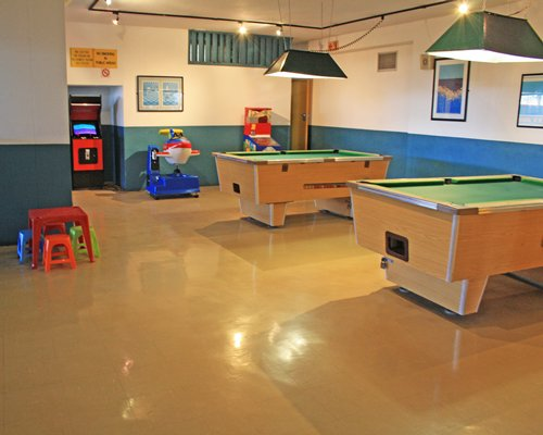 An indoor recreation area with two pool tables.