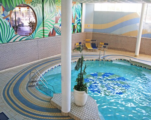 Indoor kiddie pool with chaise lounge chairs for kids.