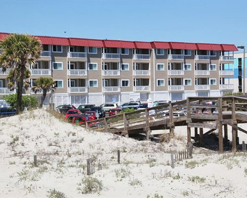 A beach view of multiple resort units alongside a wooden bridge.