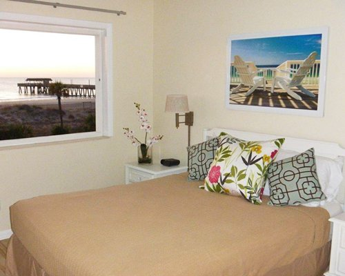 A well furnished bedroom with a queen bed and an ocean view.