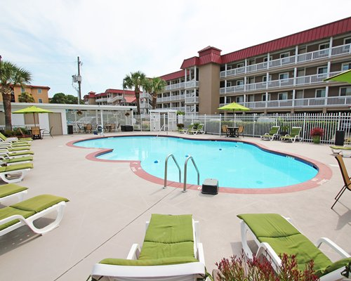 View of multiple unit balconies with outdoor swimming pool chaise lounge chairs and sunshades.