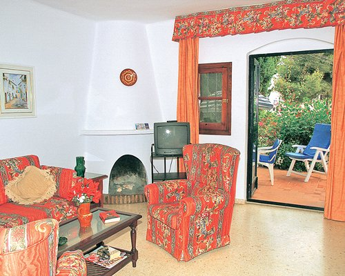 A well furnished living room with a fireplace and a television with an exterior door to the patio.