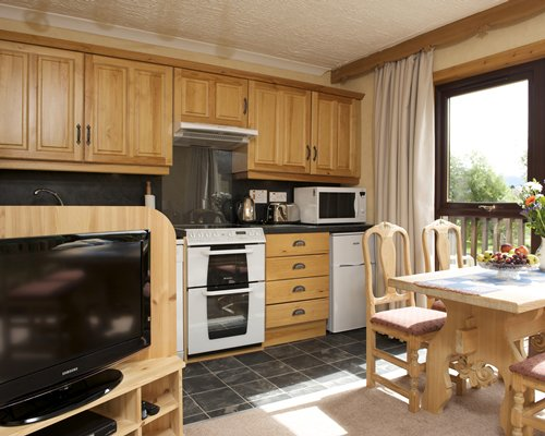 An open plan kitchen with dining area television and outside view.