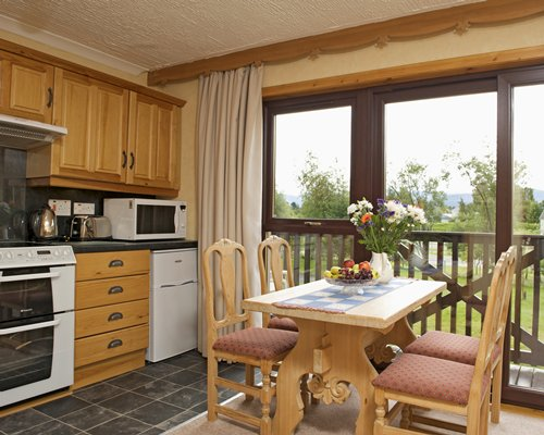 An open plan kitchen and dining area with a balcony.
