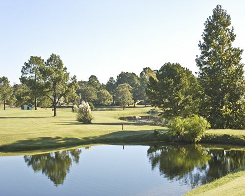 Scenic view of a golf course with a pond.