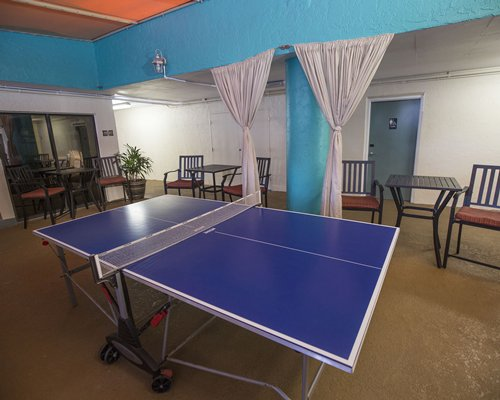 Indoor recreation room with table tennis board and patio furniture.