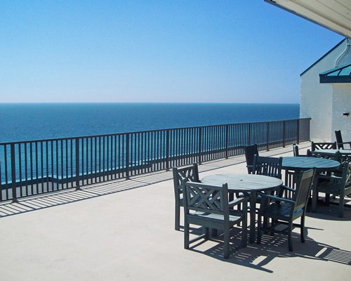 Balcony with patio tables chairs and ocean view.