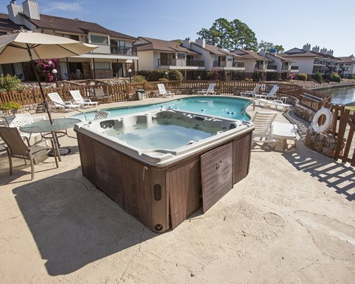 An outdoor hot tub and swimming pool with chaise lounge chairs alongside multi story condos.