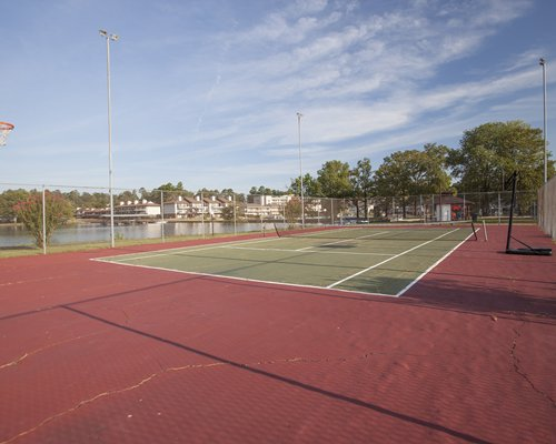 An outdoor tennis court alongside the lake.