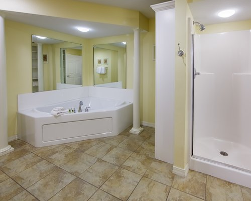 A living area alongside a bathroom with single sink vanity and a bathtub.