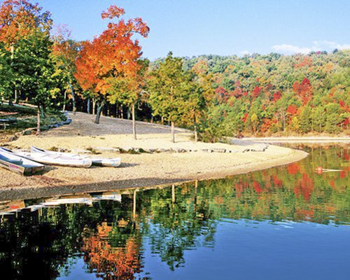 View of the lake with boats and wooded area at fall.