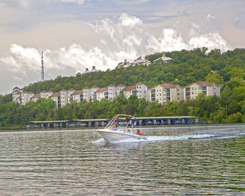A motorboat sailing on the lake alongside resort units.