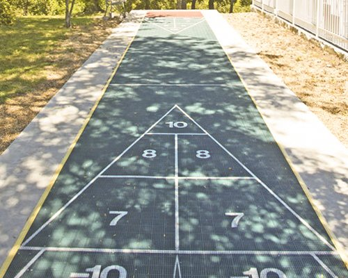 An outdoor game area with shuffle board.