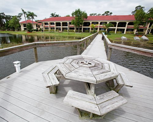 Wooden pier on the lake with patio table and pathway to Harder Hall Lakeside Villas.