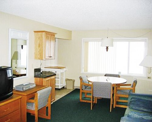 An open plan furnished living and dining area with a television.