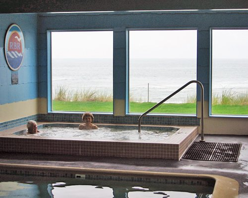 Indoor hot tub and swimming pool with ocean view.